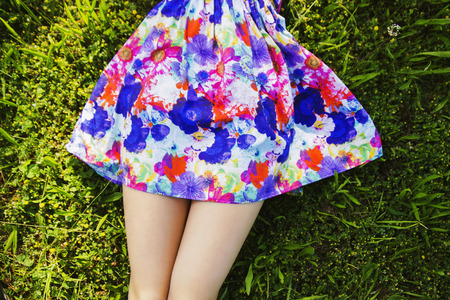 Legs and colorful skirt of girl lying in the grass