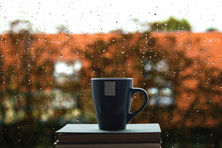 Photo pour Books and coffee on window, rain drops on glass in background - image libre de droit