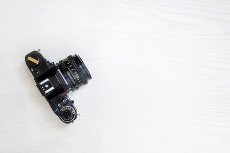 Old 35mm analog camera on white desk, isolated