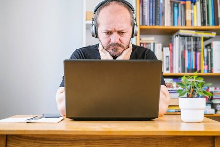 Photo pour Man working from home office, worried face expression. Adult bearded man with headphones looking worried, sitting behind vintage desk at home, working remote - image libre de droit