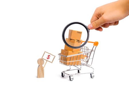 Foto de Magnifying glass is looking at a man with a poster sells goods. concept of commerce and trade, the sale and purchase of products, shopping on the Internet, deliverySupermarket cart with boxes goods - Imagen libre de derechos