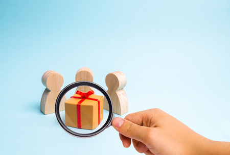 Magnifying glass is looking at the People gathered around the gift and are ready to open it. Family holiday, Christmas and New Year. Sale of gifts. Sell-out. Surprise, birthday. Christmas party