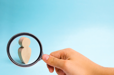 Magnifying glass is looking at the Wooden figurine of a man on a blue background. A lonely man, minimalism. Place for text. Slide for presentation.