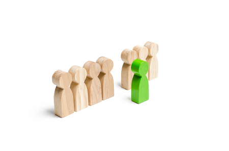 Foto de The green figure of a man comes out of the line of people. concept of success and improvement in work, the universal recognition of efficiency and leadership qualities. Talent, leader, professional - Imagen libre de derechos