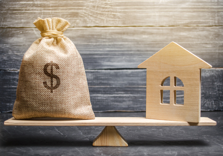 Photo pour A money bag and a wooden house on the scales. The concept of real estate purchase. Sale of property. Payment of the mortgage. Redemption of taxes. Tax refund. Legacy / Inheritance tax concept - image libre de droit