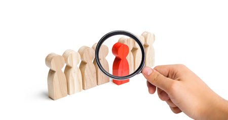 Foto de Magnifying glass is looking at the red figure of a man comes out of the line of people. Talent, leader, professional. success and improvement in work, the universal recognition of efficiency - Imagen libre de derechos