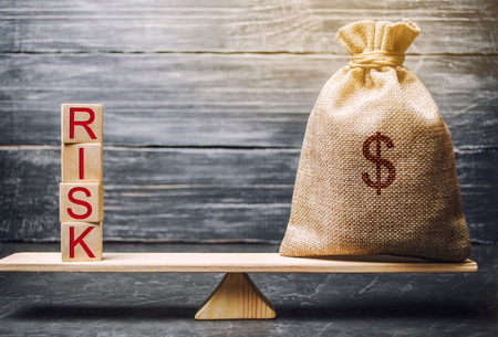 Foto de Money bag and wooden blocks with the word Risk. The concept of financial risk. Justified risks. Investing in a business project. Making the right decision. Property insurance. Legal and market risks - Imagen libre de derechos