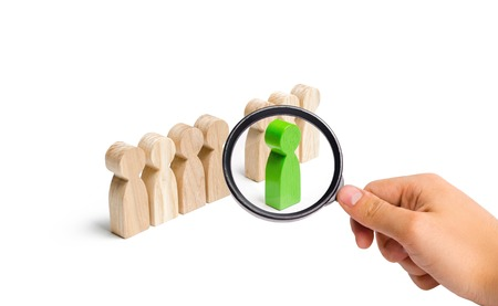 Foto de Magnifying glass is looking at the green figure of a man comes out of the line of people. concept of success and improvement in work, the universal recognition of efficiency and leadership qualities. - Imagen libre de derechos