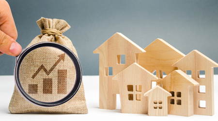 Photo pour Money bag with chart up and wooden houses. The concept of real estate market growth. The increase in housing prices and rent. Growing demand for property purchase. Rising interest rates on mortgages - image libre de droit