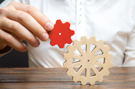 Photo for Businessman connects a small red gear to a large gear wheel. Symbolism of establishing business processes and communication. Increase efficiency and productivity. The best business formula for success - Royalty Free Image