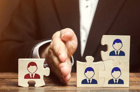 Foto de The leader separates the puzzle with the image of the employee. The concept of personnel management in the company. Dismissing an employees from a team. Demotion. Bad worker. Staff cuts - Imagen libre de derechos