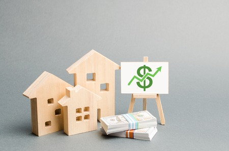 Foto für Wooden figures of houses and a poster with money. The concept of real estate value growth. Increase liquidity and attractiveness of assets. Raising the rent or cost of buying a home. - Lizenzfreies Bild