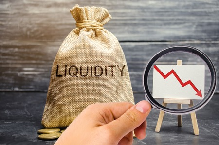 Foto de Falling liquidity and profitability of stocks and investments. Recession. Low attractiveness of short-term deposits. Financial crisis. The collapse of the securities market. Money bag, down arrow - Imagen libre de derechos