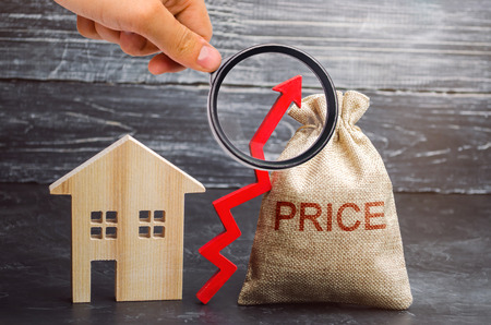 Photo for Bag with the money and the word Price and up arrow and wooden house. The increase in housing prices. Rising in fees for an apartment. The rise in property prices. The growth of utilities - Royalty Free Image