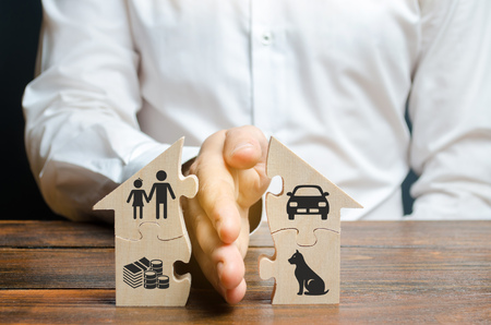 Photo for A man shares a house with his palm with images of property, children and pets. Divorce concept, property division process. Marriage contract, custody of children. The layer's services - Royalty Free Image