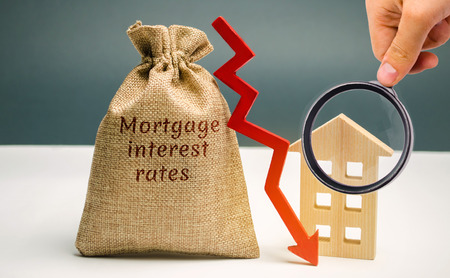 Photo for Bag with the money and the word Mortgage interest rates and arrow to down and house. Low interest in mortgages. Reducing interest payments for mortgages. The fall in housing rates on credit. Low housing demand - Royalty Free Image