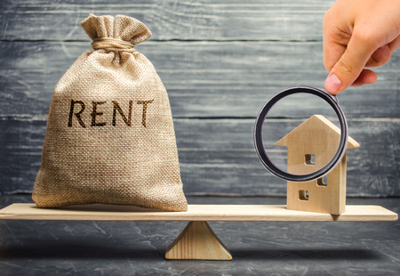 Photo pour Money bag with the word Rent and a wooden house on the scales. The concept of payment for rental housing. Debt repayment. To renting a house. Rent a property. Court, Law and Justice - image libre de droit
