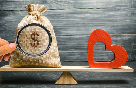 Photo pour Bag with money and red wooden heart on the scales. Money versus love concept. Passion versus profit. Family or career choice. Family psychology. Mind vs. Passion - image libre de droit