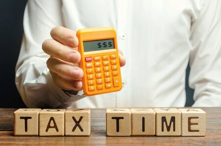 Wooden blocks with the word Tax time and taxpayer with a calculator. The concept of paying the tax rate. Taxation / burden. Pay off debts. Property / income annual taxes. Dollars on the screen