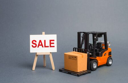 Photo for Orange forklift truck carries a cardboard box and a stand with a word sale. growth of sales. big discounts on goods of the outgoing season. commodity exchange with other countries. Attracting buyers - Royalty Free Image