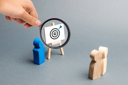 Photo pour Magnifying glass is looking at leader explains employee tactics of advertising targeting. Training, briefing. Search strategies for effective advertising campaigns, customer reach. Business processes - image libre de droit