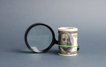 Photo pour Magnifying glass and a bundle of money. Concept of fundraising, attracting investments. Loan to paycheck, urgent loans. The study of sources of profit, money laundering, offshore. Financial monitoring - image libre de droit