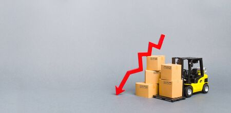 Photo pour Yellow Forklift truck with cardboard boxes and a red arrow down. Concept drop in industrial production, business. economic downturn. Production, purchasing power. Reduced storage. Banner, copy space - image libre de droit