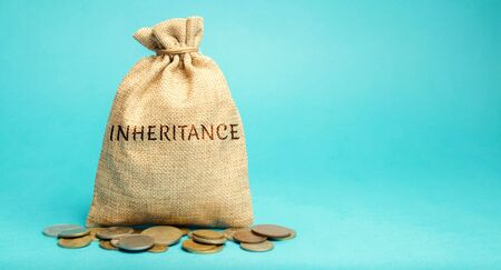 Photo pour Money bag with the word Inheritance. Separation of inheritance between relatives or transfer of property to charitable organizations. Payment of taxes. Investment funds. - image libre de droit