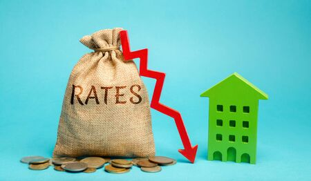 Photo for Money bag with the word Rates, down arrow and wooden house. The concept of reducing interest rates on mortgages. Low rental rate for housing. Real estate market and loan. - Royalty Free Image