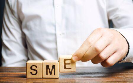 Photo pour Businessman holds wooden blocks with the word SME. Small and medium-sized enterprises - commercial enterprises that do not exceed certain indicators. - image libre de droit