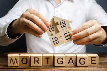 Photo pour A man collects a house from the puzzles over the inscription Mortgage. Construction of your own residential building. Buying a home on credit loan, improvement of living conditions - image libre de droit
