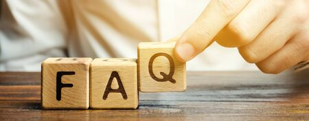 Photo pour Businessman puts wooden blocks with the word FAQ (frequently asked questions). Collection of frequently asked questions on any topic and answers to them. Instructions and rules on Internet sites - image libre de droit