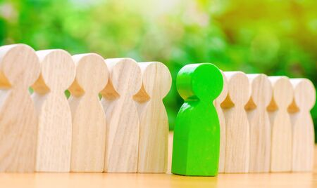Photo pour Wooden figures of people. The green man comes out with a team of workers. The concept of choosing a new leader. Choice of person. Hiring and recruiting. Talented employee. Demote. Selective focus - image libre de droit