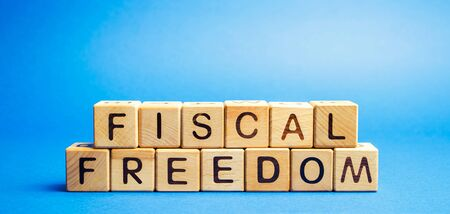 Wooden blocks with the word Fiscal freedom. Tax burden imposed by government. Taxation. Taxes concept. Business and Finance