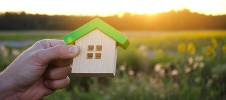 Foto de Wooden house in the hands in the sunset background. Real estate concept. Eco friendly home. Symbol of happy family life. Buy a housing outside the city. Search for hotel on vacation. Selective focus - Imagen libre de derechos