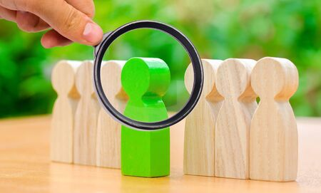 Foto de Wooden figures of people. The green man comes out with a team of workers. The concept of choosing a new leader. Choice of person. Hiring and recruiting. Talented employee. Demote. Selective focus - Imagen libre de derechos