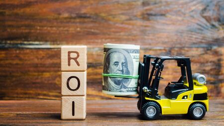 Wooden blocks with the word ROI and money with forklift. Ratio between the net profit and cost of investment resulting from an investment of resources. High level of business profitability.