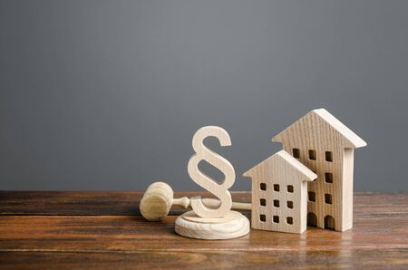 Foto de Wooden houses and paragraph figurine with judge hammer. Litigation in housing and real estate disputes. Norms and rules for construction, maintenance. Encouraging green and energy-saving technologies - Imagen libre de derechos