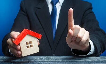 Foto de Man with a house makes a gesture of attention. Legal advice on terms a contract deal for purchase of real estate, lending and mortgage loan. Warning, indicate the nuances. Warn about risk of threat. - Imagen libre de derechos