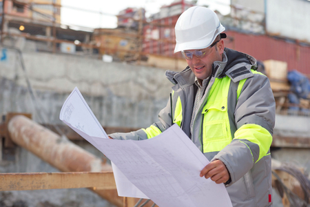 Civil Engineer at at construction site is inspecting ongoing production according to design drawings.