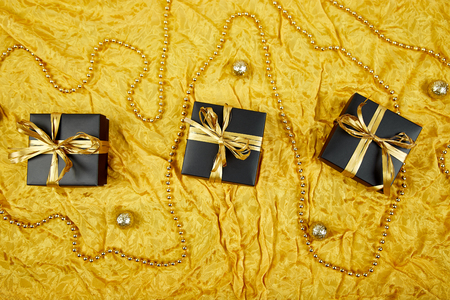 Luxury black gift boxes with gold ribbon on shine gold background. Christmas, birthday party. Flat lay. Copy space. Top view.