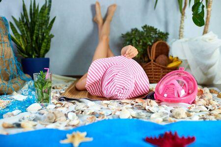 Foto de The girls in pink hat is lying on a fictional beach near the sea or ocean, sunbathes. Imitates summer sea beach vacation at home quarantine. Coronavirus home activity, funny, happy, crazy. - Imagen libre de derechos