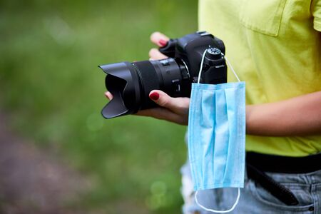 Photo for Woman photographer with a photo camera in hand outdoor with protection mask coronavirus, World photographer day, copy space, Photography Concepts Professional in pandemic. - Royalty Free Image