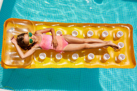 Photo pour Little girl in sunglasses relaxing in swimming pool, enjoying suntans, swims on inflatable yellow mattress and has fun in water on family vacation, tropical holiday resort, view from above, copy space. - image libre de droit