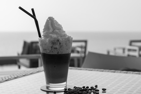 Coffee frappe with beautiful sea in background  - monochrome