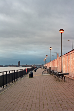 Promenade on the River Mersey, Liverpool, UK, with ferry crossing the river at sunset