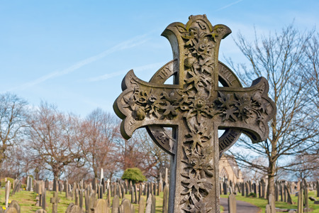 A cross in an ancient graveyard with tombstones in the background