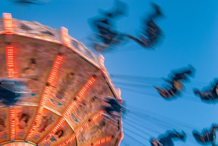 Photo for Amusement park motion blurred riders on retro vintage tilting swing against clear blue sky. - Royalty Free Image