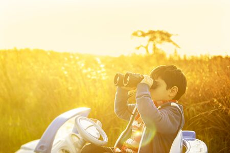 Photo pour young boy ventures out into the world with his toy car, in a rural setting at sunset - image libre de droit