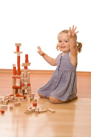 Happy little girl playing with wooden blocks on the floor - isolated